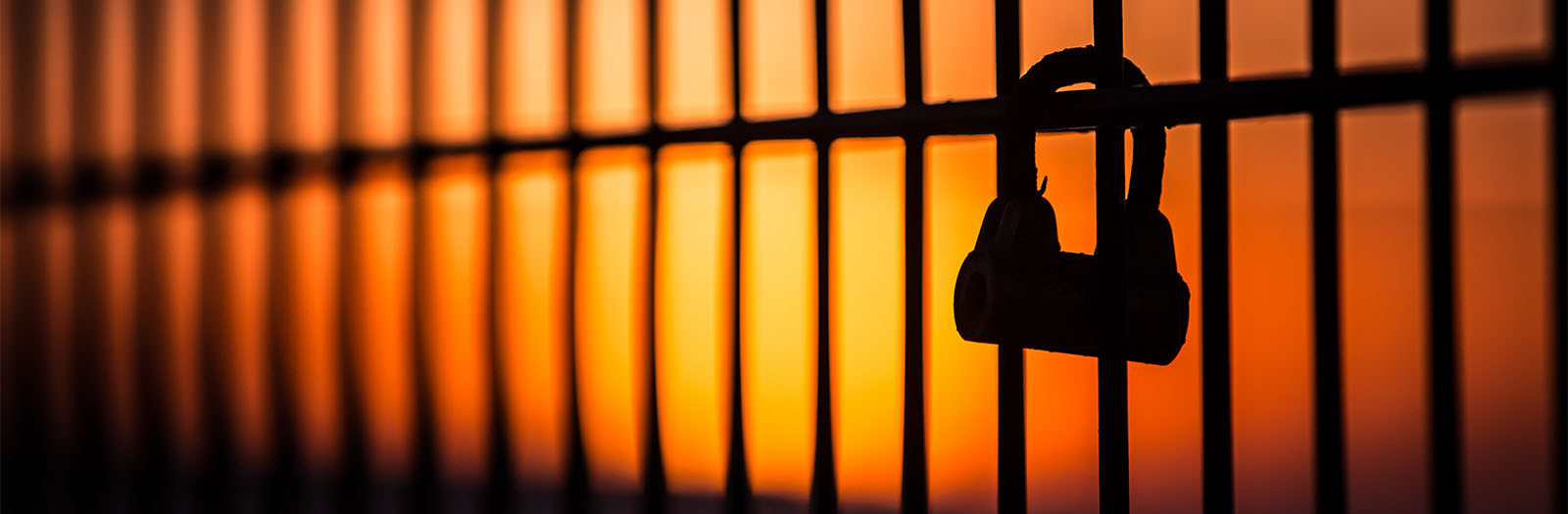 photo of bars with a lock at sunset