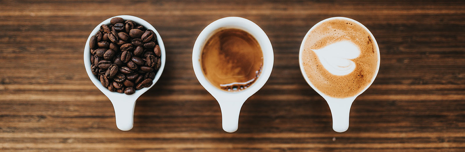 image of three cups containing coffee beans, espresso and cappuccino