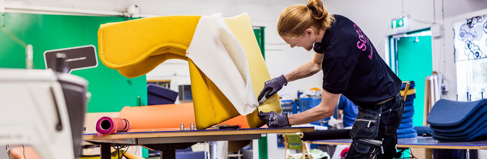 worker reupholstering armchair