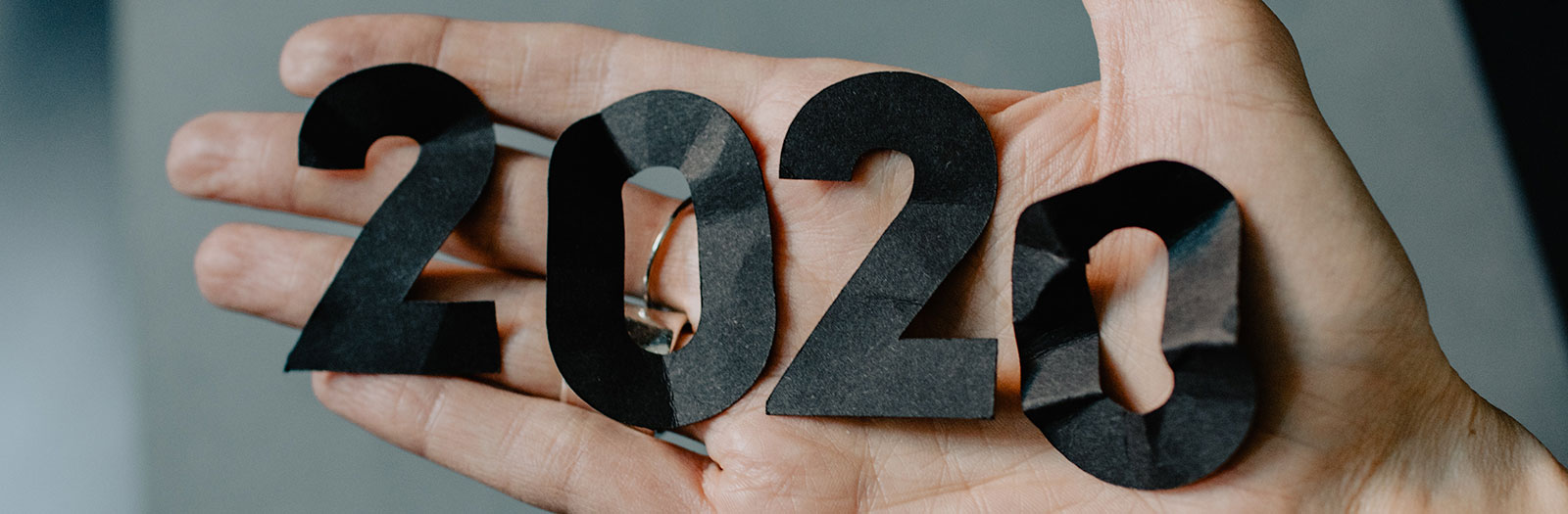 """photo of hand holding paper numbers that spell """"2020"""""""