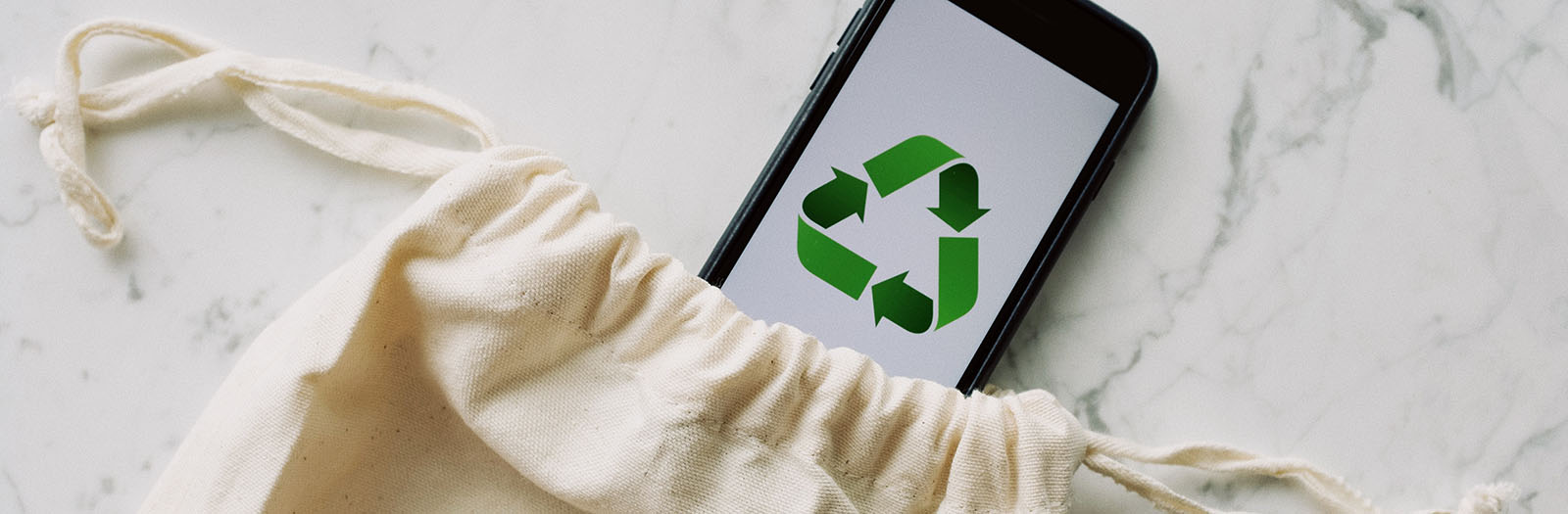 photo of a cell phone with a recycling logo placed within a reusable bag